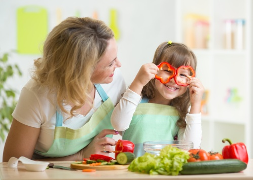 mother and her child preparing healthy food and having fun