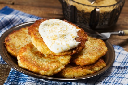 Homemade potato pancakes served with sour cream and brown sugar