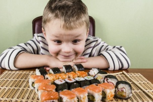 Boy eats a lot of sushi