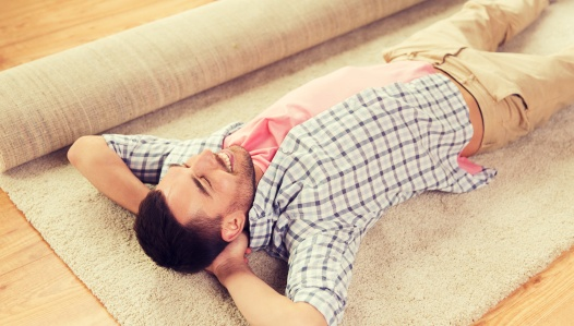 happy man lying carpet or rug at home