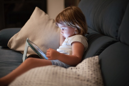 blonde three years old baby shirt and shorts, sitting comfortably in sofa inside home at night reading and watching digital tablet, face illuminated by the light of the screen